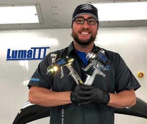 Danny Rodriguez holding his spray paint guns and Luma lights.